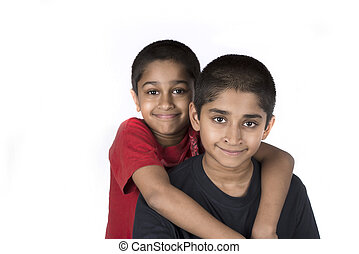 Brothers - Indian brothers smiling happily against a white...