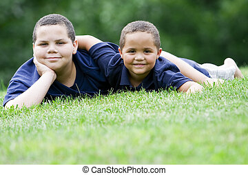 Brothers - Two brothers lying on their fronts on fresh green...