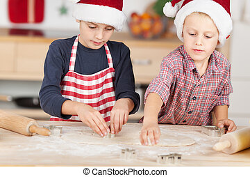 Brothers Using Cutters On Dough To Make Christmas Cookie -...