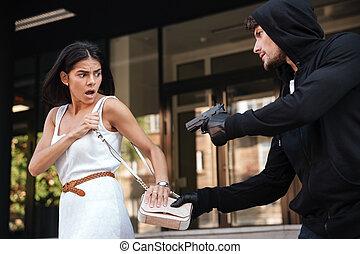 brottsling, man, med, gevär, stöld, väska av, rädd, ung kvinna