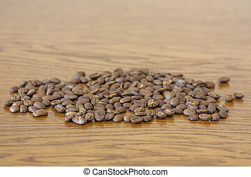 Broun coffee beans isolated on brown wooden texture...