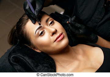 Beautician applying white pencil and blending with a brush. Preparing to a powder sputtering permanent brow makeup