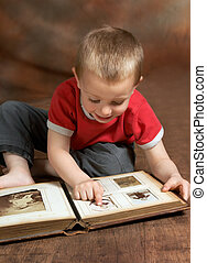 Young boy browsing an antique family album (the faces on the photos in the album cannot be recognized)