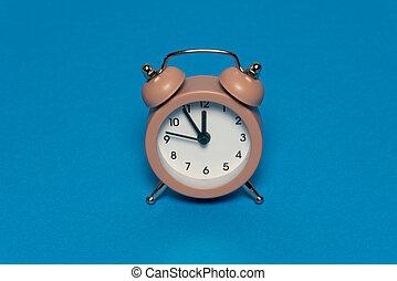 Brown alarm retro clock on blue background. Five minutes to twelve