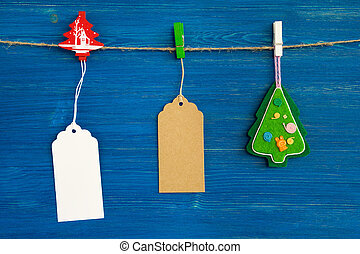 Brown and white blank paper price tags or labels set and Christmas decoration hanging on a rope on the blue wooden background.