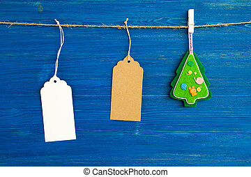 Brown and white blank paper price tags or labels set and Christmas felt decoration hanging on a rope on the blue wooden background.