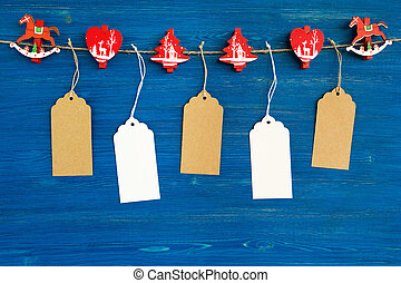 Brown and white blank paper price tags or labels set and Christmas wooden decoration hanging on a rope on the blue wooden background.