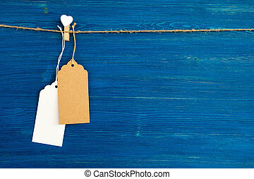 Brown and white blank paper price tags or labels set and wooden pin decorated on white heart hanging on a rope on the blue wooden background.