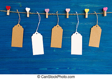 Brown and white blank paper price tags or labels set and wooden pins decorated on colored hearts hanging on a rope on the blue wooden background.