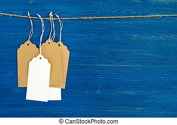 Brown and white blank paper price tags or labels set hanging on a rope on the blue wooden background.
