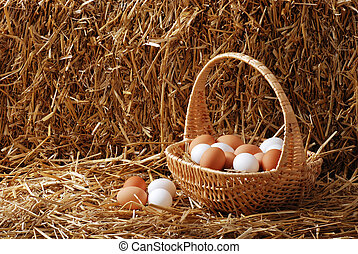 Brown and white eggs in a basket on straw