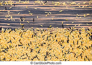 brown and wild rice on a zebrano wooden background