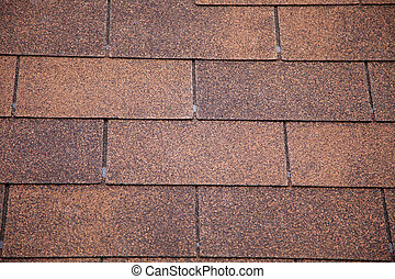 brown asphalt roofing shingles. - A close-up of brown toned...