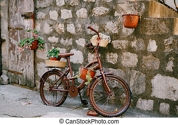 Brown bike with flower stands against the brick wall.