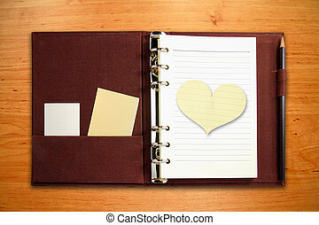 Brown binder notebook with blank heart shape paper on wooden background