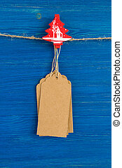 Brown blank paper price tags or labels set and Christmas wooden decoration hanging on a rope on the blue wooden background.