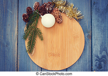 brown board with Christmas decoration on blue wooden background