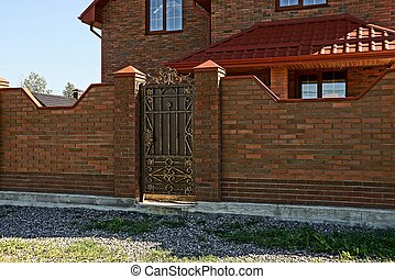 Brown brick fence and a door with a private house near the road