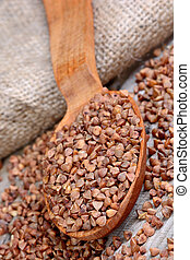 Brown buckwheat in a wooden spoon