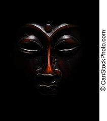 brown budda mask black  in black background