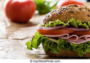 brown bun ham sandwich on paper