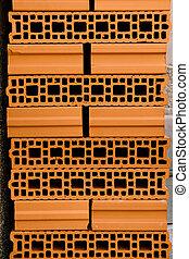 Brown ceramic cladding brick with empty holes.