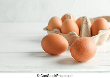 Brown chicken eggs in carton box on white background, space for text and closeup