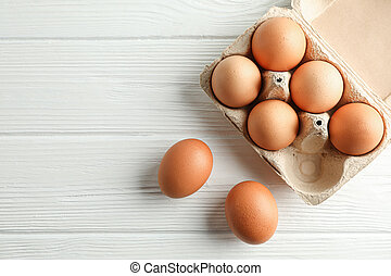 Brown chicken eggs in carton box on white background, space for text and top view
