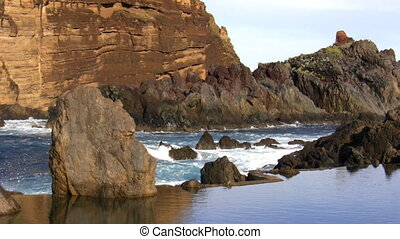 Brown cliffs and calm lagoon - Two level water surface -...