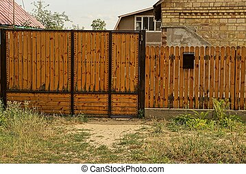 brown closed wooden gate and part of the fence of boards outside in the grass