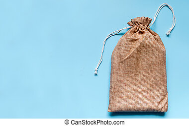 Brown cloth bag on blue background. The bag is covered with white lines.