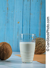 Brown coconut fruit and a glass of milk on blue background