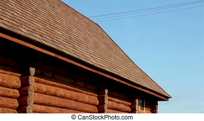 Brown colored log house with tar oiled cedar wooden shingle roof where you can see the dark brown edges of the roof and even the outside walls of the cabin.