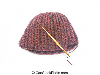 Brown crochet hat with golden hook isolated on white background.
