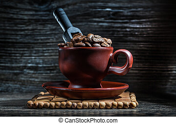 brown cup with coffee beans and black little scoop.
