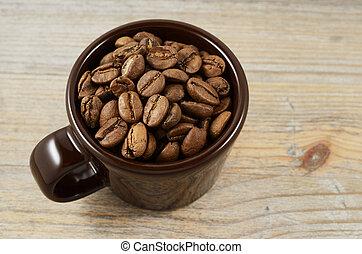 brown cup with coffee beans