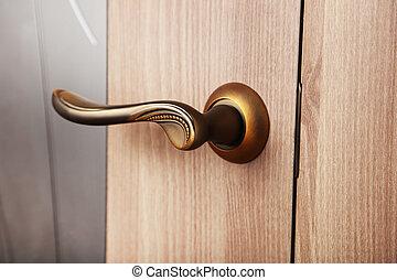 Brown door handle on wooden door