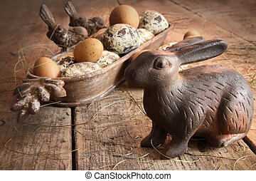 Brown easter eggs with antique bunny on wood