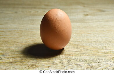 brown egg shell with shadow on wooden table background