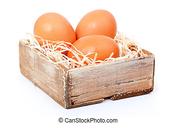 brown eggs at hay, in the old box, on white background