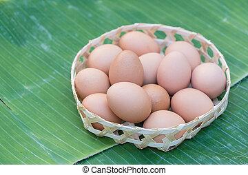 Brown eggs in the basket on banana leaf