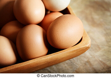 Brown eggs in wooden bowl on wooden table