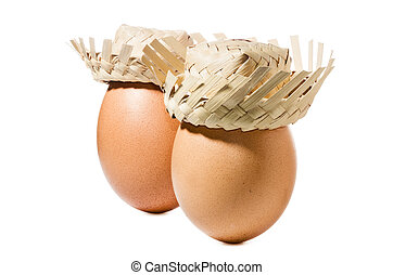 Brown eggs with straw hat isolated on white background
