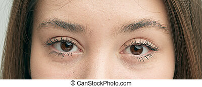 Brown eyes of a beautiful emotional girl close-up.
