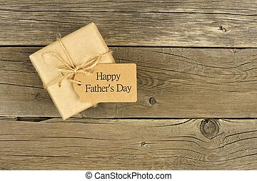 Brown Fathers Day gift box with tag on a rustic wood background