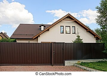 brown fence and metal gate in the street and a big house