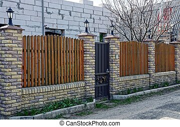 brown fence made of bricks and wooden boards with a closed door