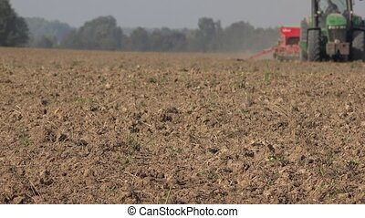Brown field soil and blurred tractor with seeder work on...