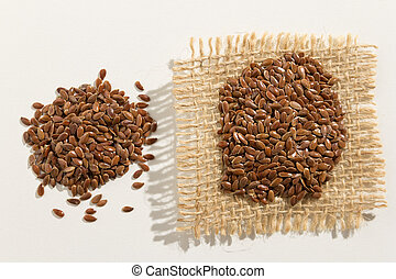 Brown Flax seed. Close up of grains spreaded over white table.