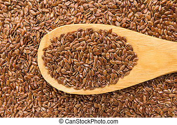 Brown Flax seed. Grains in wooden spoon. Close up.